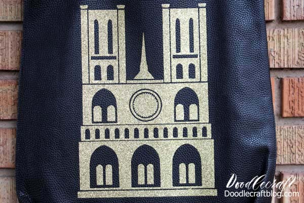 Cricut Maker cut gold iron on vinyl in intricate silhouette of Notre Dame Cathedral and adhered to black leather tote bag using the EasyPress 2 large heat press.