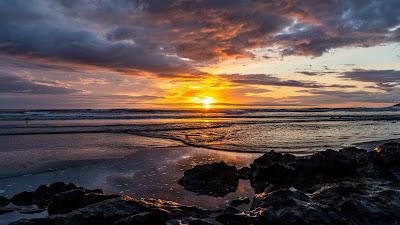 Beautiful sunset clouds, beach, stones, skyline