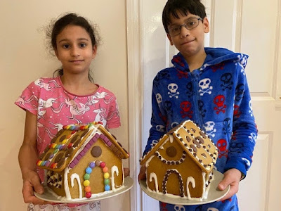 Two children holding gingerbread houses