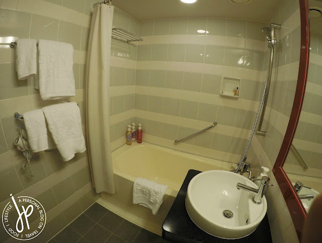 hotel bathroom with toilet, sink, shower, and bathtub