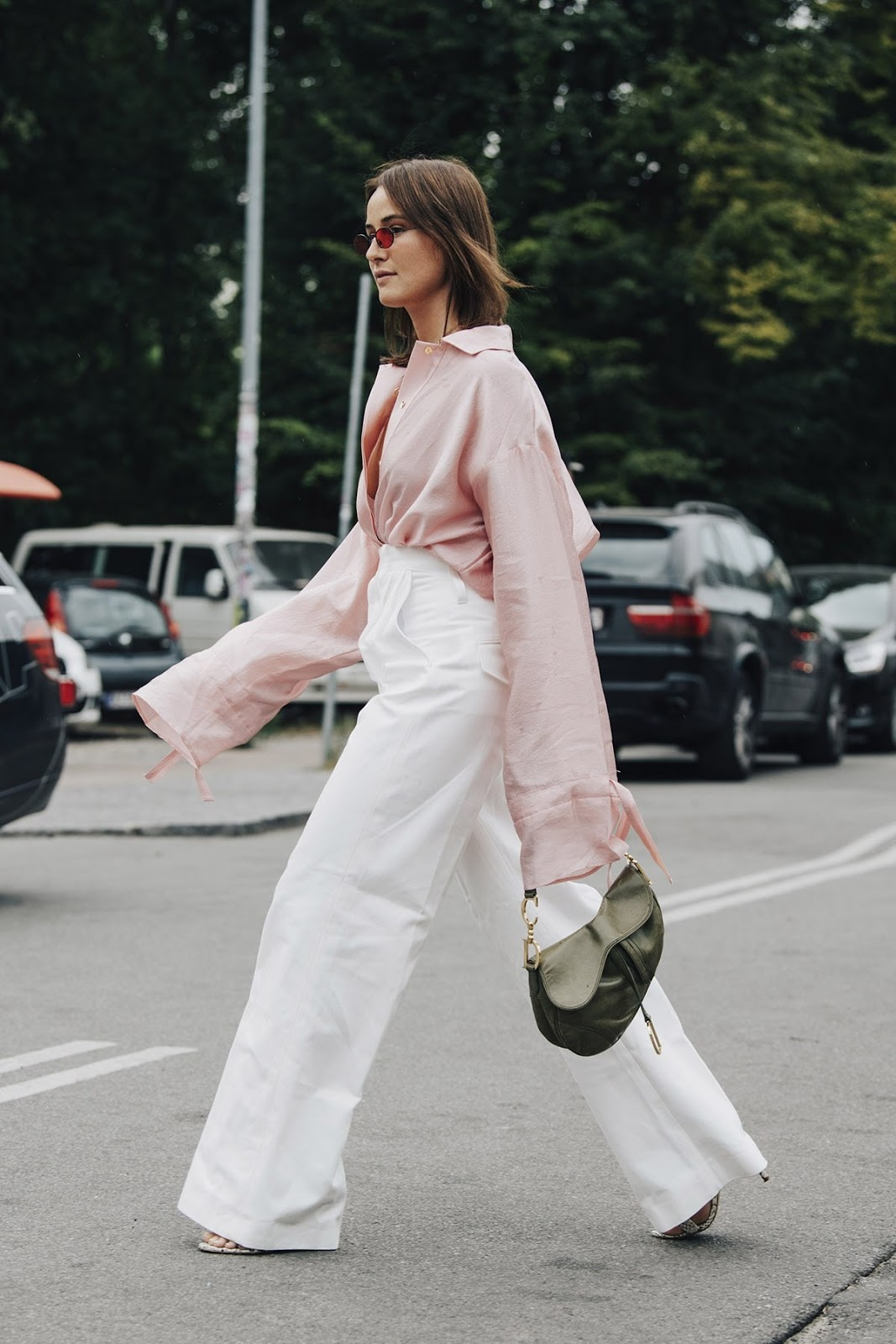 25 Cool Pink Tops to Wear for Spring and Beyond — Street style outfit with a pink button-down, white wide-leg pants, and green Dior saddle bag