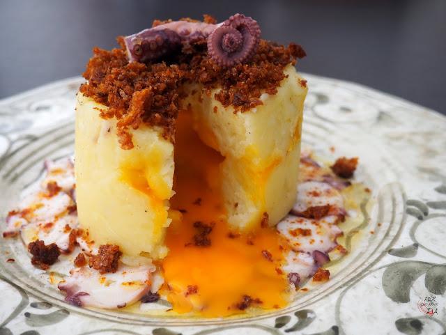 Coulant de puré de patata, con cremosa yema de huevo en su interior, sobre carpaccio de pulpo y coronado con migas de pimentón
