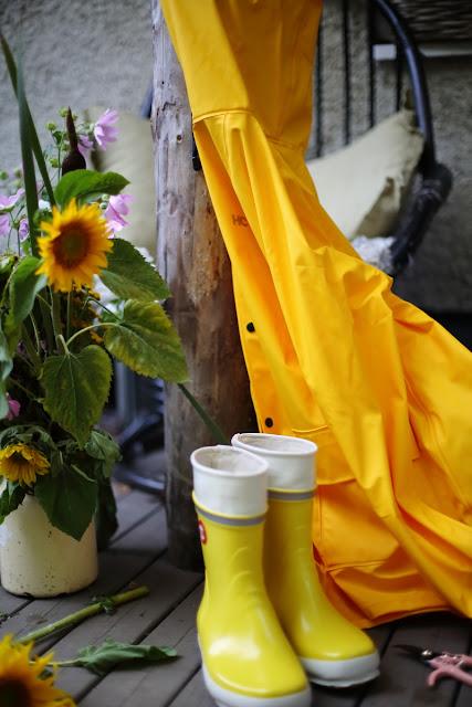 keltaiset Hai-saappaat, sadetakki, aurongonkukka