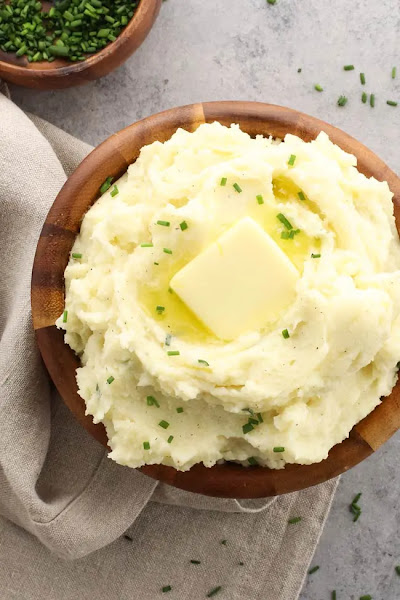 Top view of sour cream and chive mashed potatoes in a wodden bowl.