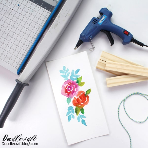 Supplies needed for a hanging scroll sign: Wood game piece, watercolor floral art, hot glue and hot glue gun, bakers twine and paper cutter.