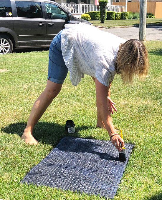 woman painting a mat