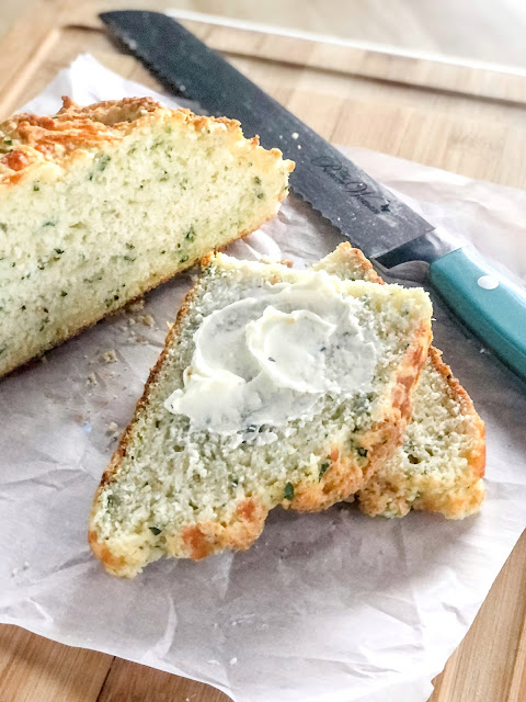 cheese herb bread with butter on parchment paper