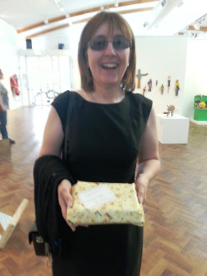 Woman in an art gallery holding a gift wrapped in paper printed with flowers.