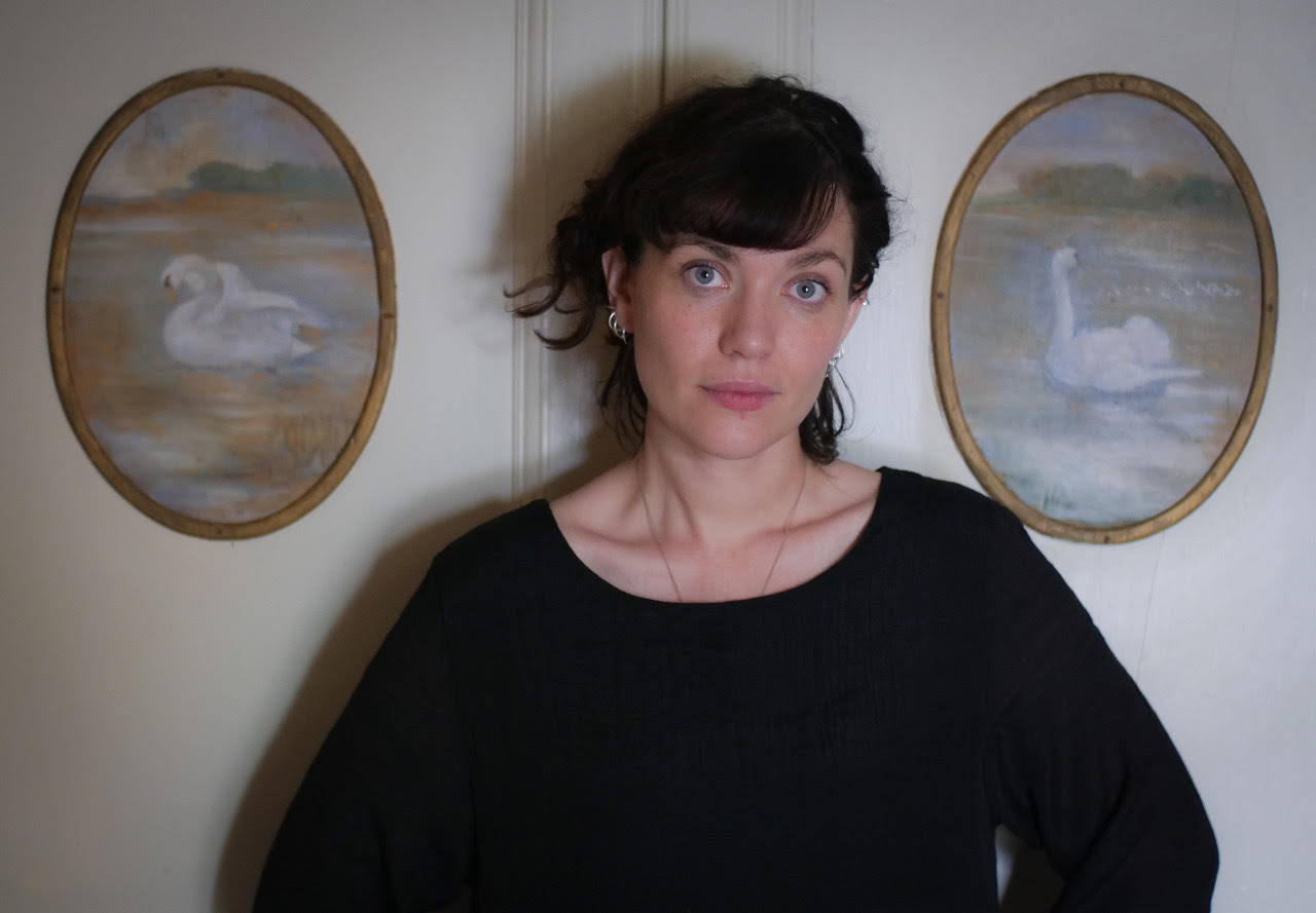 A photo of Deirdre Sullivan between two framed paintings of swans on a white wall