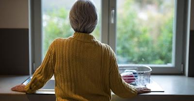 Dona d'esquenes  mirant a una finestra