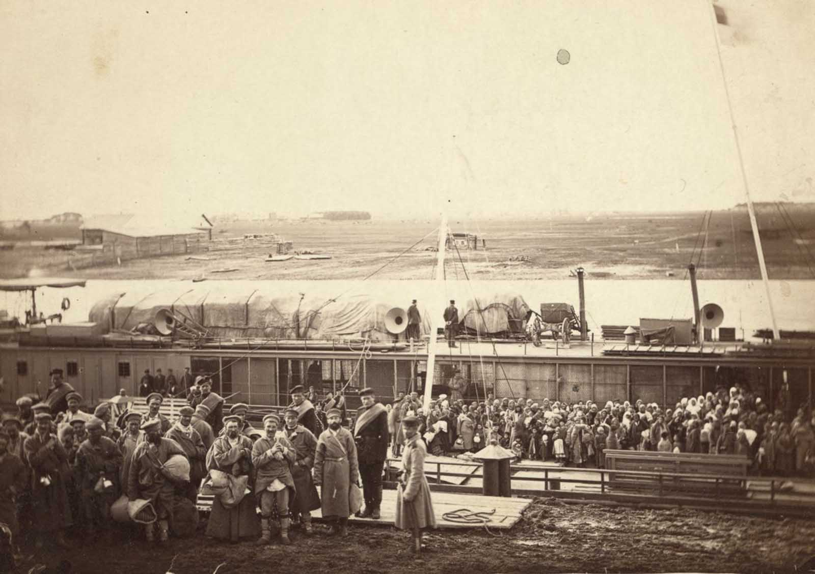 Exiles and convicts wait at Tyumen wait to board a prison barge for Tomsk. Many are joined voluntarily by their wives and children.
