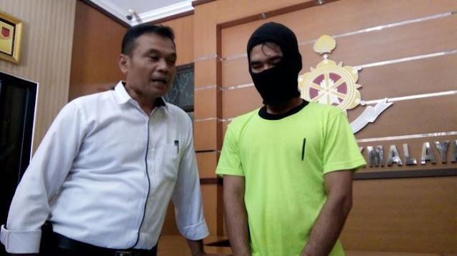 FS (26) tersangka penyebar berita hoax (kanan) dan Kasatreskrim AKP Pribadi, saat ditemui di ruang reskrim Mapolres Tasikmalaya. Image: Tribunnews.com