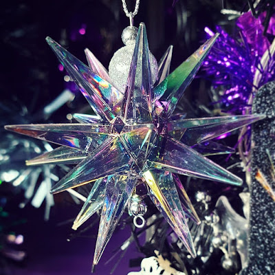 A bauble in the shape of a jaggedly pointed star with many points, made of clear plastic with an iridescent rainbow finish that tends towards green and purple. The bail for suspending the bauble is two silver beads It is infront of the black Christmas tree and a dark purple wall. Bright purple tinsel is visible