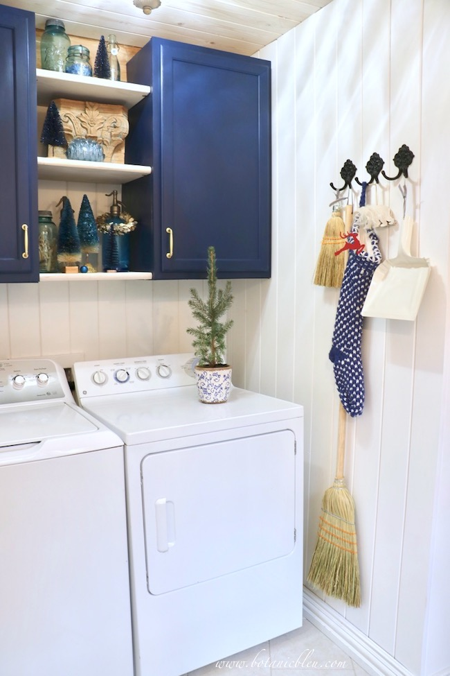 Blue Christmas Laundry Room decorated with a blue and white knit stocking hanging from black iron hooks