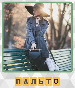 на скамейке осенью сидит девушка в пальто и шляпе с сумочкой