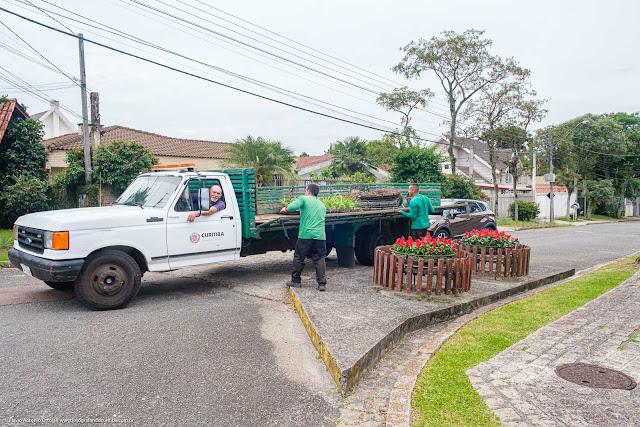 Trabalhadores com caminhão substituindo vasos de flores