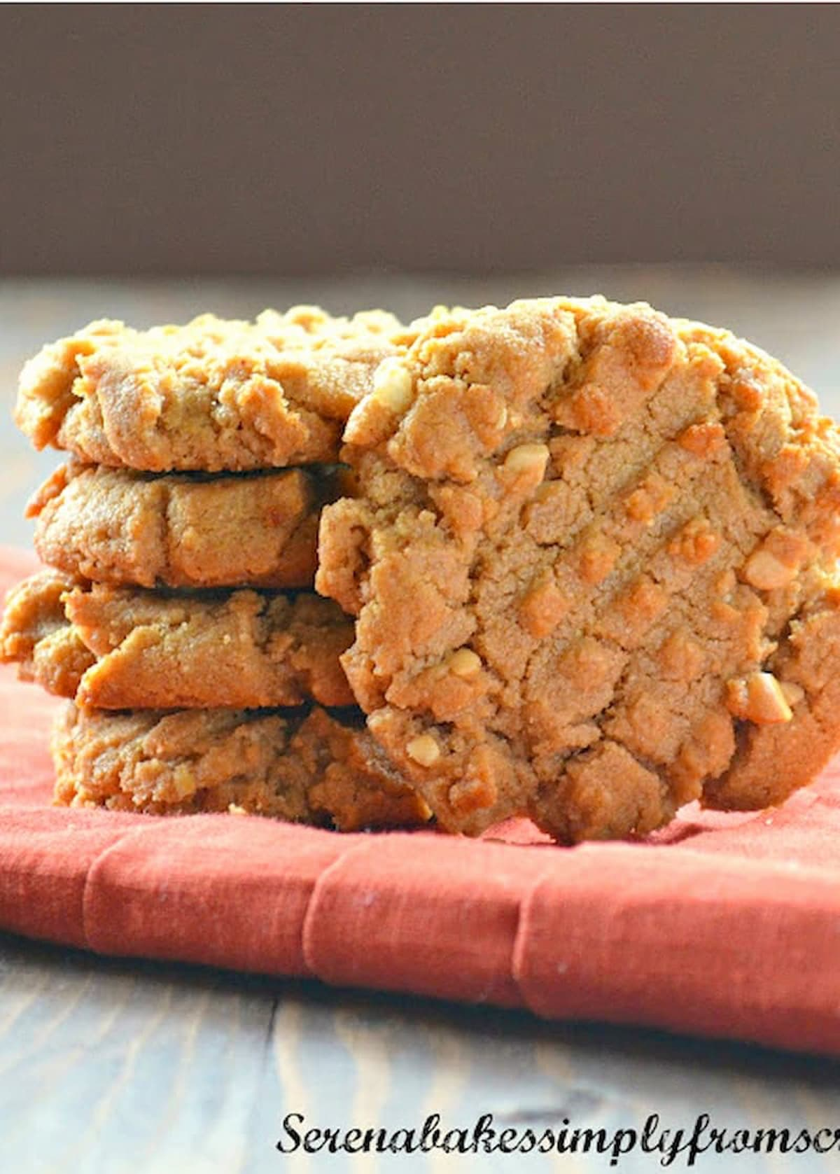 Flourless Peanut Butter Cookies stacked 3 high on an orange napkin with 1 standing up in front.