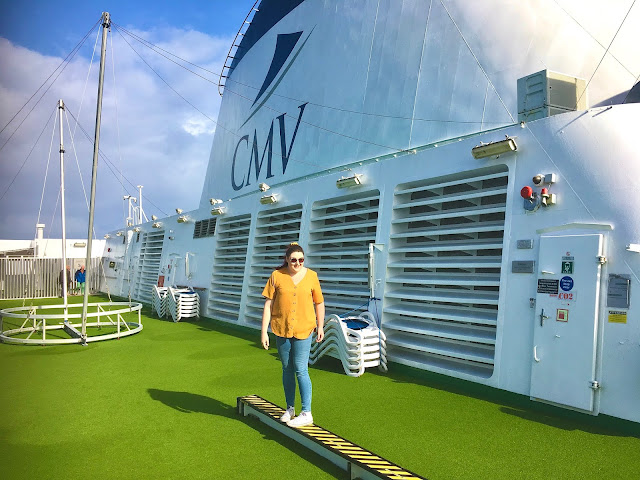 Plus size blogger The Owlet stood by the funnel on a cruise ship