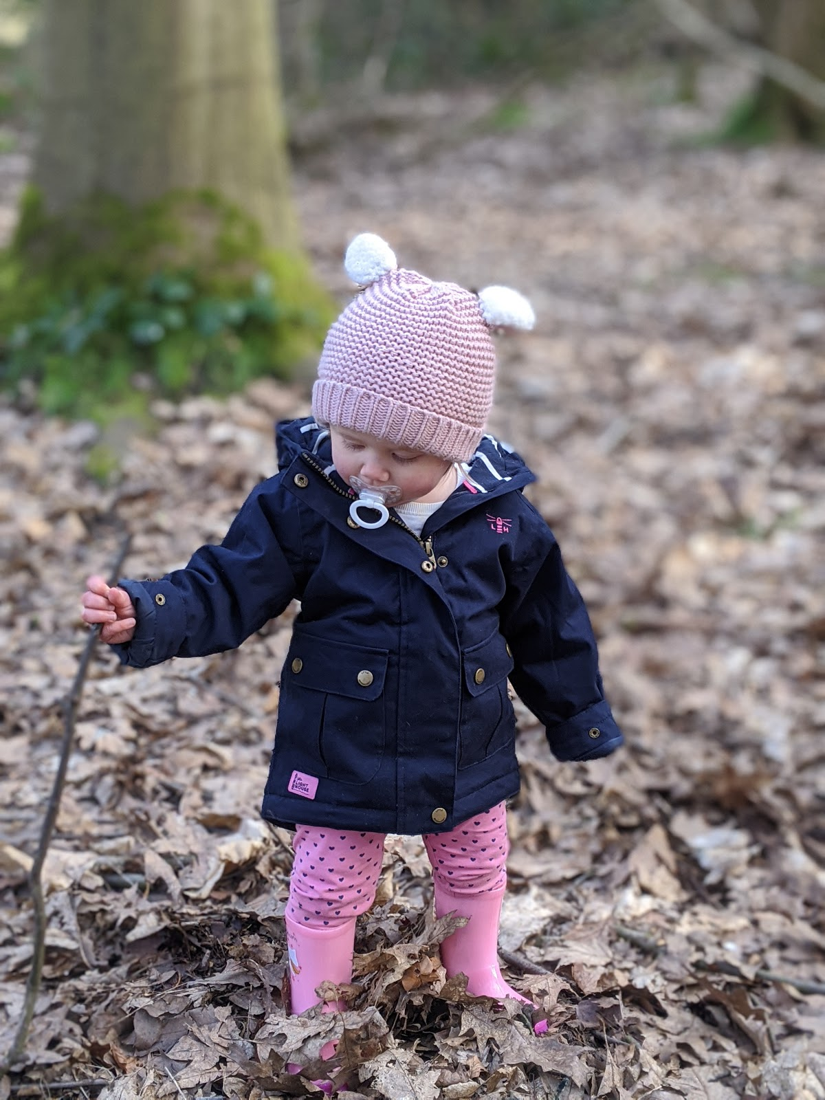 Toddler wearing navy Lighthouse raincoat with pink bobble hat.