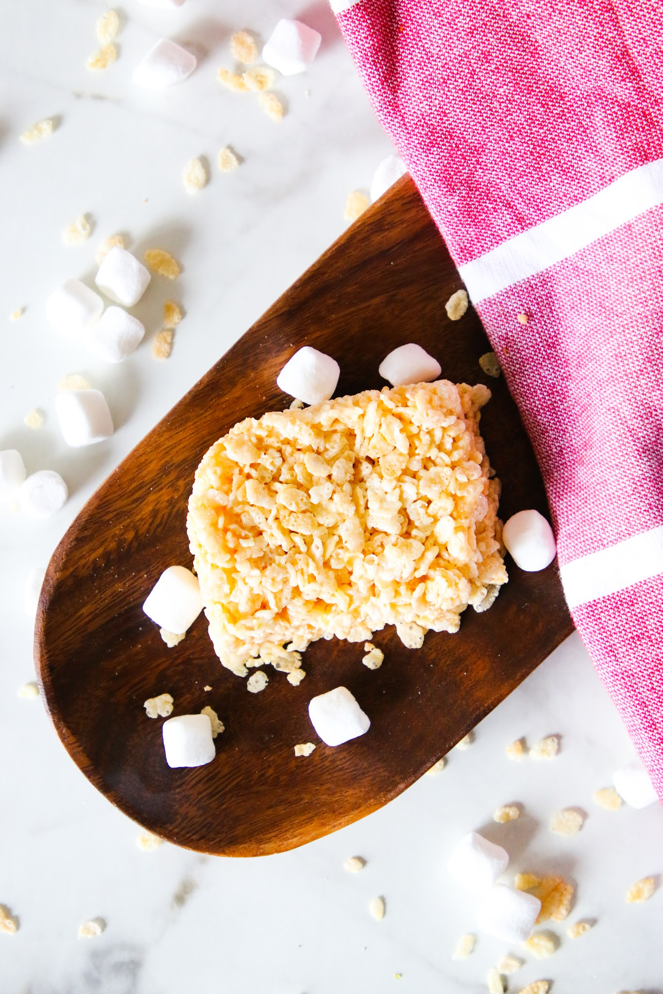 Rice krispie treat on a wood platter with a red dish towel with rice krispies and marshmallows scattered on the table