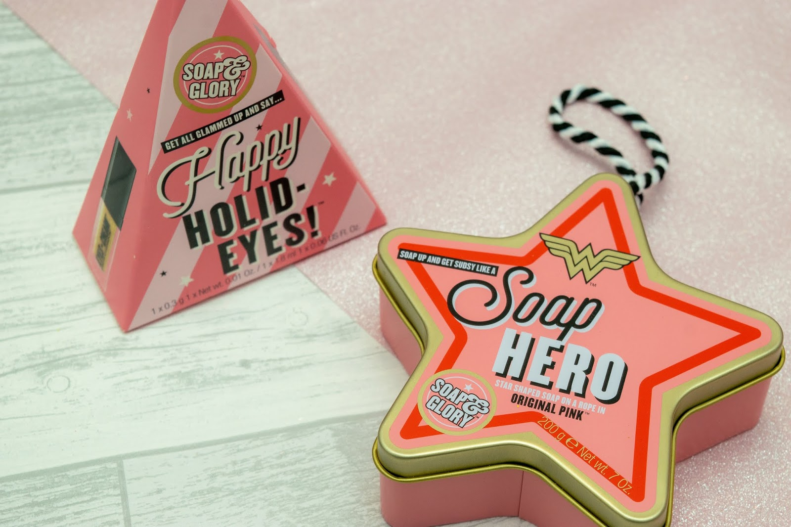 A rectangular based pyramid box with the words Happy Holid-Eyes on the front with a loop on top and a metal star tin with the words Soap Hero on and with a loop on top.