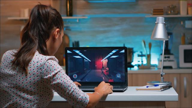 امرأة شابة تلعب على جهاز كمبيوتر محمول