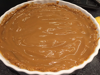 Caramel layer of the Banoffee Pie in a white dish