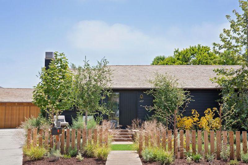 Aspecto exterior de la pequeña casa de campo de madera, pintada de negro.