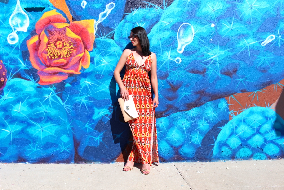 This is a photo of me wearing an orange maxi dress, with a beautiful blue and orange mural in the background.