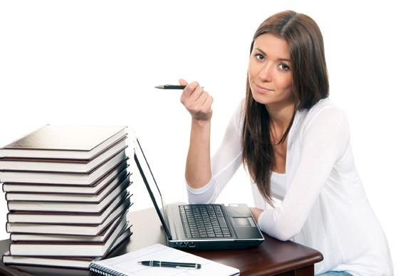 Femme écrivant à la main devant son ordinateur.