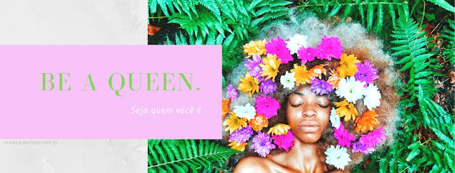 """Capa para facebook feita com o Canva. Uma mulher negra com o cabelo todo recoberto por flores, sob um fundo de folhagens verdes com a frase: """"Be a Queen - Seja quem você é"""""""