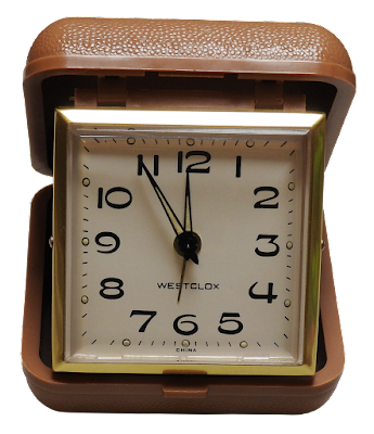 A vintage fold-up Westclox travel alarm clock in brown case.