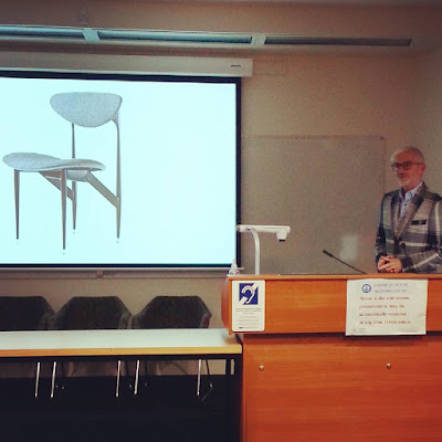 Geoff Isaac giving a talk in front of a slide of a Scape dining chair by Grant Featherston.