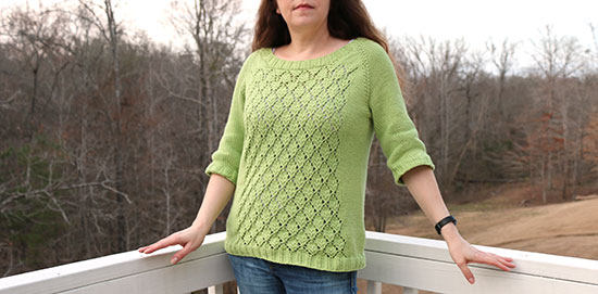 Woman standing in front of a white porch rail wearing a hand-knit spring green lace sweater, with leafless trees and brown grass in the background.
