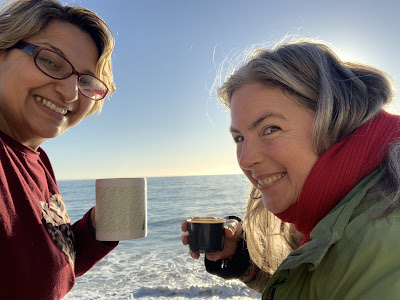 two women on rocks by sea driving coffee out of mud and thermos.