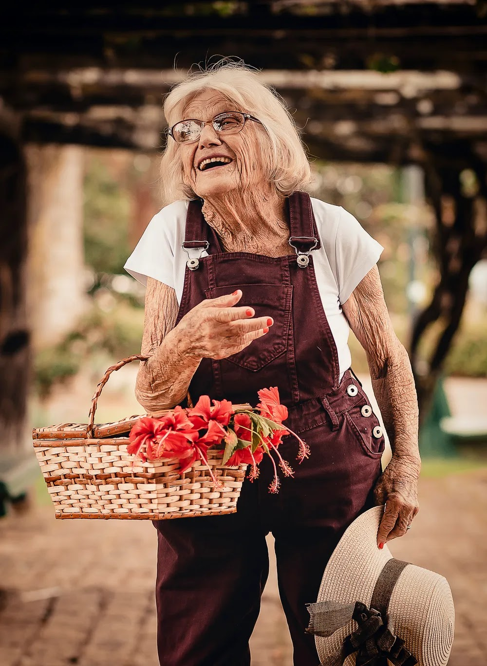Stock photo from pexels of an elderly lady in red dungarees holding a basket of flowers