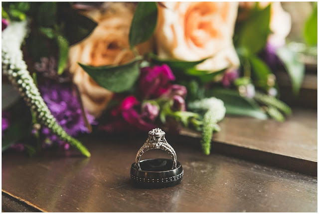 photo of wedding rings with bouquet