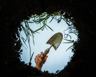 A hand holding a trowel over a hole. The view is from the ground up.