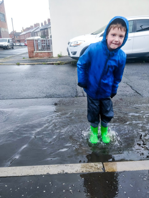 Dark blonde haired boy with hazel eyes wearing a blue winter coat, navy waterproof trousers and bright green wellington boots is standing in a puddle which has several small splashes coming over his boots. In the background you can see cars parked on the other side of the street and the street corner with houses bending round into a diagonal line.