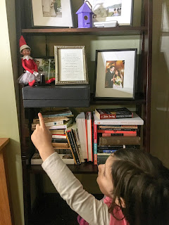 Young female pointing to Elf on the Shelf sitting on a bookshelf.