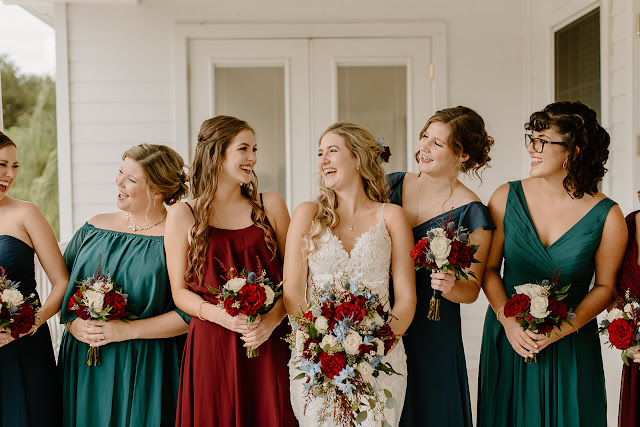smiling bride and bridesmaids in red and blue colors