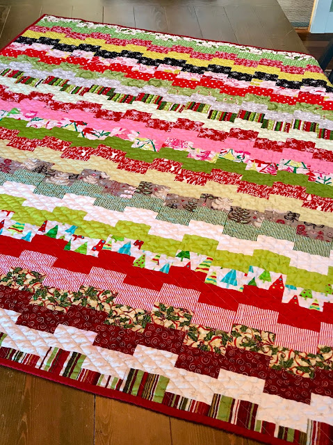 photo of multi-colored quilt from christmas fabrics laying on wooden table