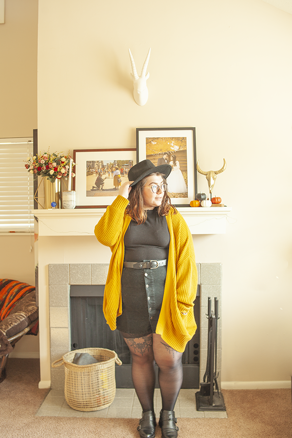 An outfit consisting of a black wide brim hat, black mockneck short tucked into a black button down skirt, black sheer tights and black ankle boots..