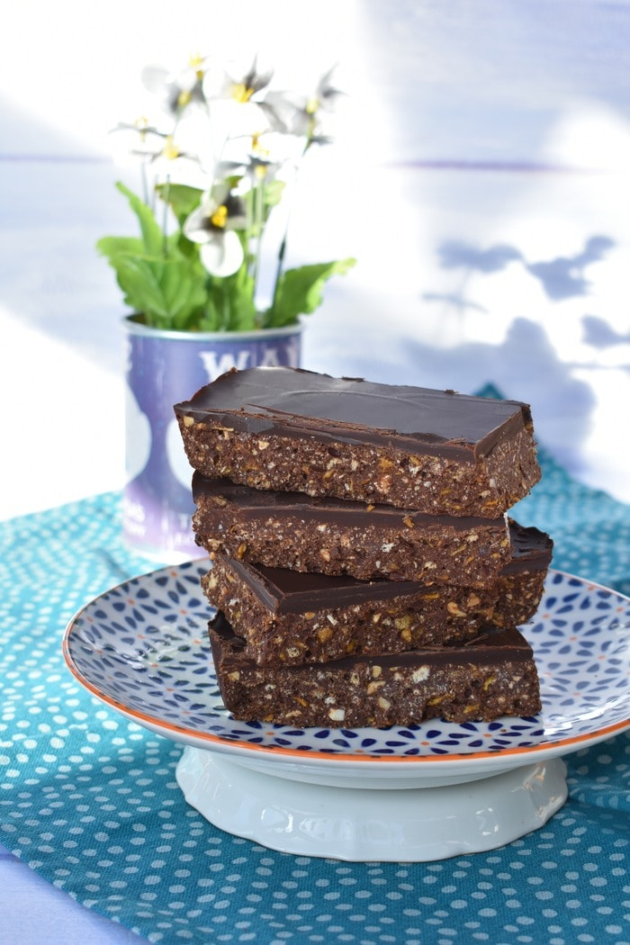 Stack of No Bake Peanut Butter & Cornflake Chocolate Tiffin on blue and white patterned plate with pot of white daisies in background.