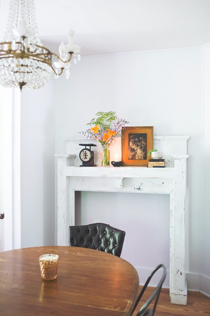 salvaged mantel in dining room with crystal chandelier