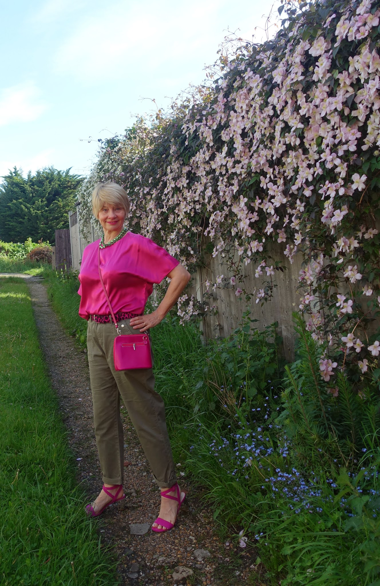 Over 50s blogger Gail Hanlon in khaki cargo trousers and bright pink silk blouse against a clematis montana backdrop