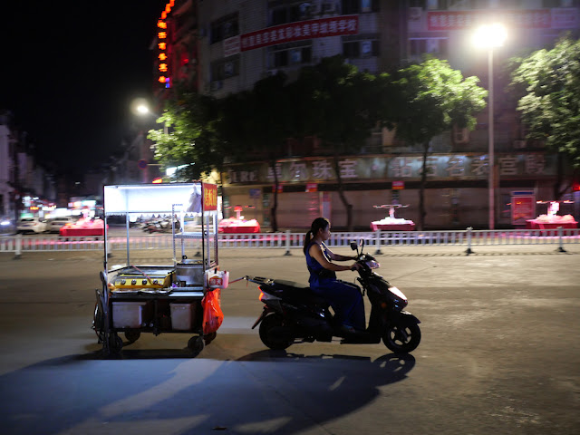 woman on motor scooter towing a food cart
