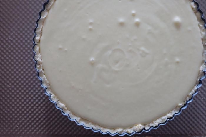cheesecake filling in tart pan ready to bake