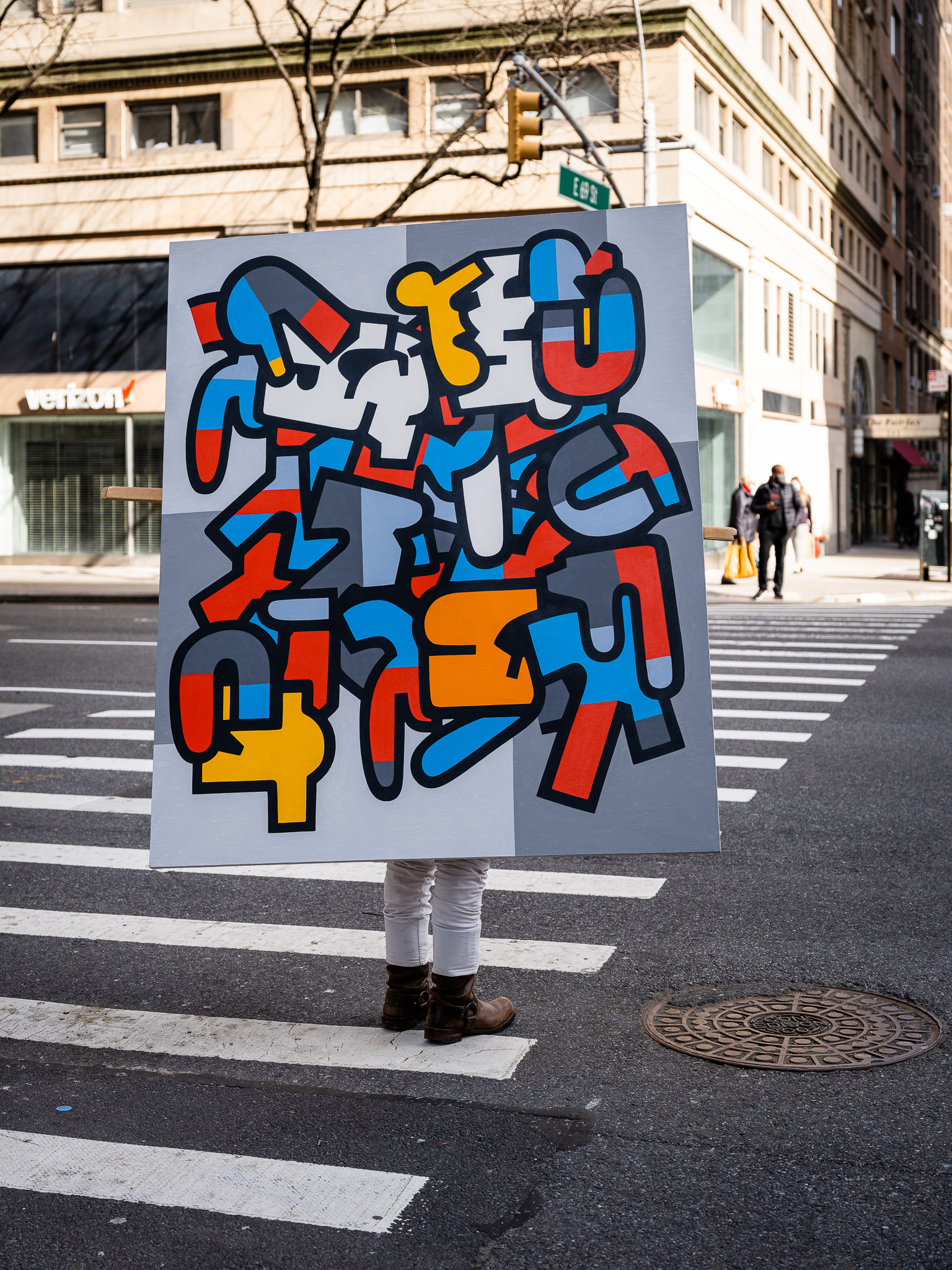 a photo of a person carrying a painting across the street in new york city