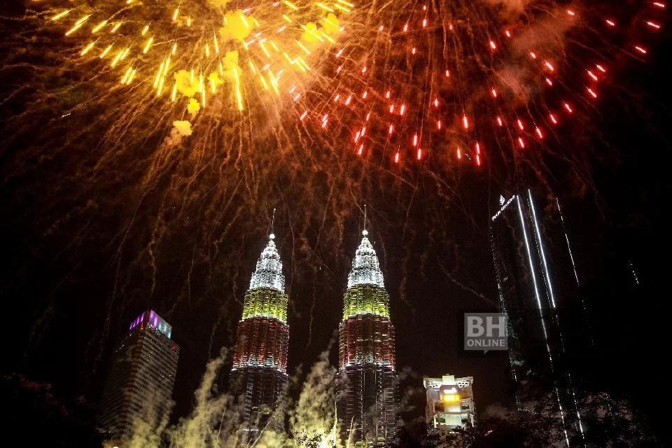 The fireworks display at the National Day celebration threshold is behind the Petronas Twin Towers that feature the color of the Gemilang at Suria KLCC.
